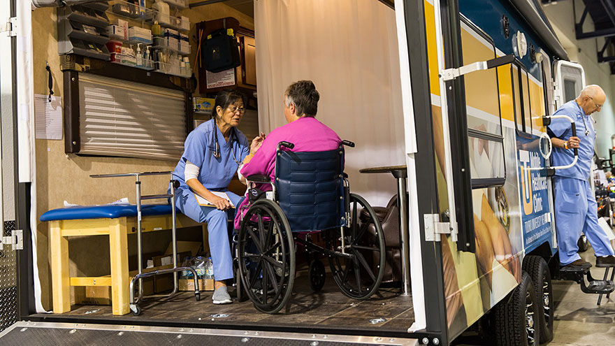 A patient and a provider inside the Mobile Health Clinic.