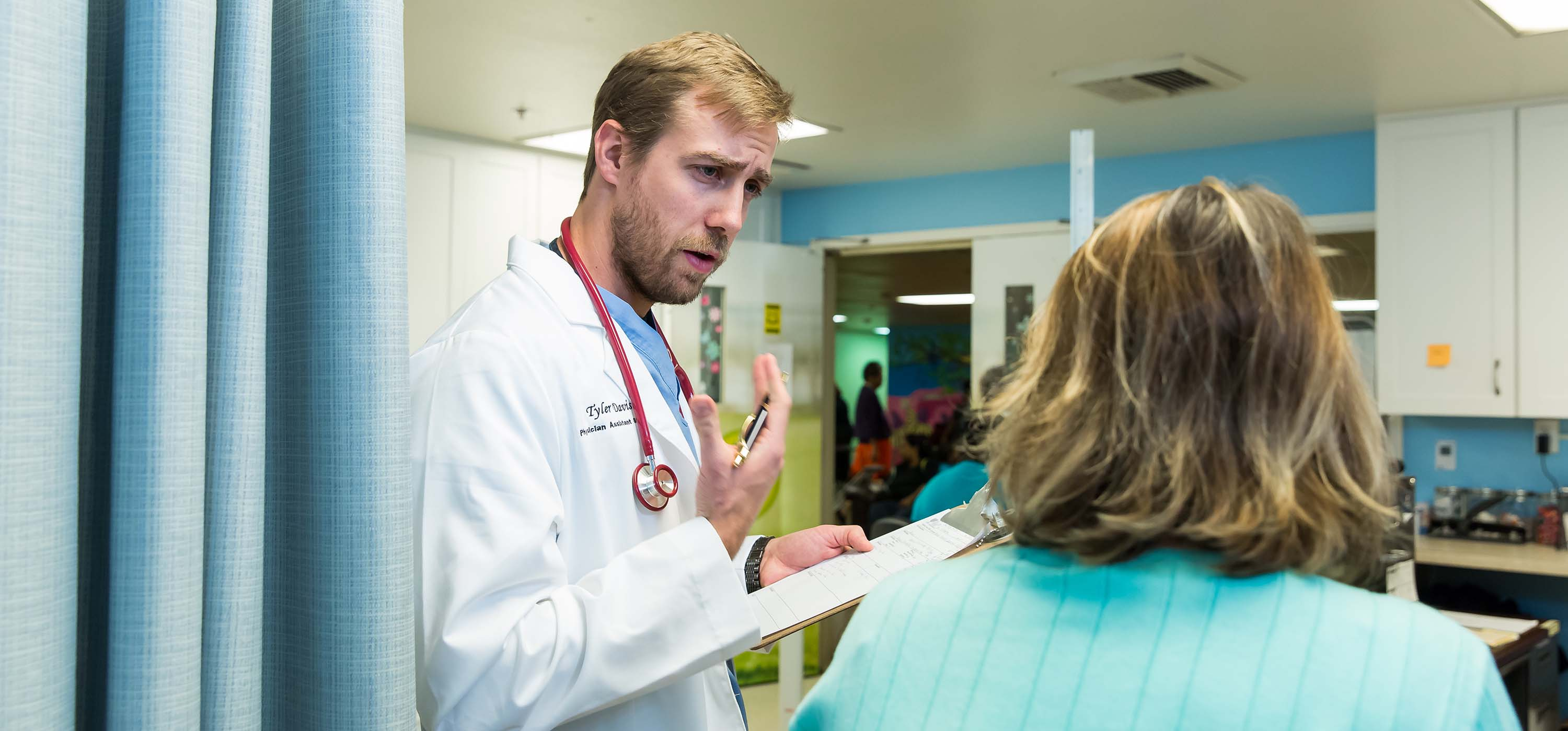 A physician assistant studies student talks to a patient.
